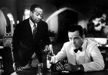 Rick Blaine (Humphrey Bogart) contemplates his dilemma in Casablanca watched over by his trusty pianist, Sam.