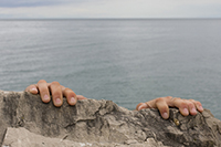 Life is hard - hands grasp desperately to the top of a cliff face